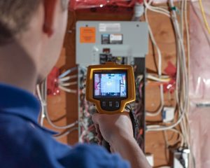 Boris Vorobyov inspects electrical panel with thermal sensor device